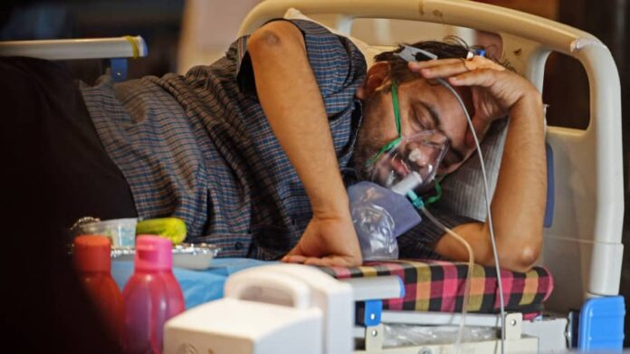 Man in India lying in a hospital bed